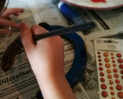 Schön kreativ bemalen die Kids ihre Hufeisen.